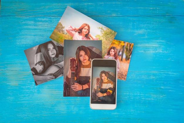 Kolorowe fotografie młodej dziewczyny i telefonu komórkowego z jej wizerunkiem na niebieskim drewnianym stole.