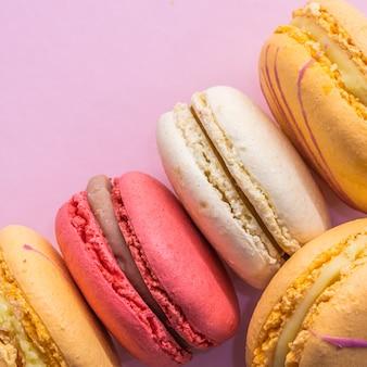 Kolorowe francuskie ciasteczka makaroniki na różowym tle smaczne owocowe migdałowe słodkie ciasteczka ciasto makaron