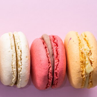 Kolorowe francuskie ciasteczka makaroniki ustawione na różowym tle smaczne owocowe migdałowe słodkie ciasteczka