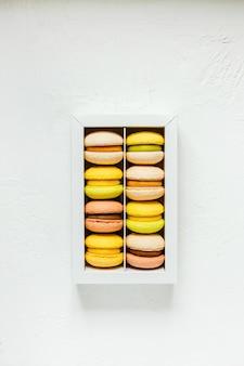 Kolorowe francuskie makaroniki w białym pudełku na biały, widok z góry