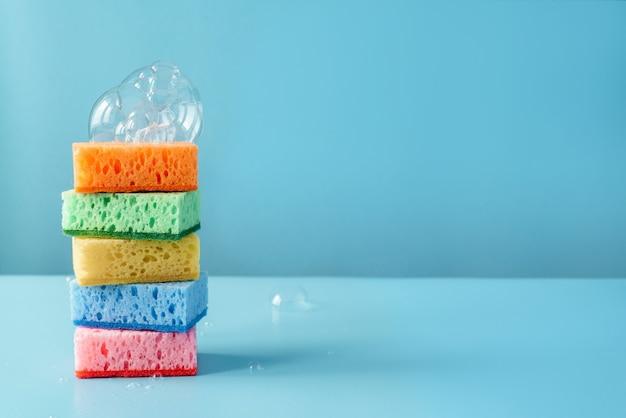 Kolorowe gąbki czyszczące z bańkami mydlanymi na niebieskiej ścianie