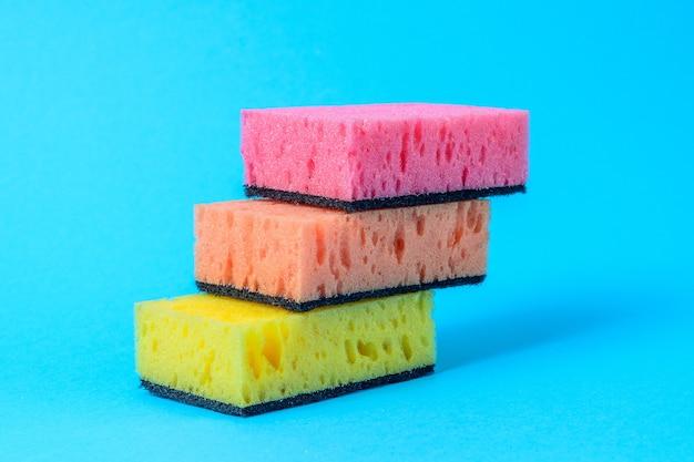 Kolorowe gąbki do mycia naczyń ułożone są stopniowo na niebieskim tle.
