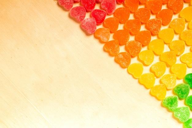 Kolorowe galaretki i cukierki słodycze w kształcie serca na tle drewna