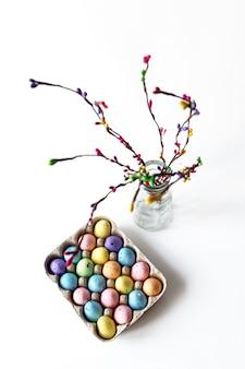 Kolorowe gałązki wierzby i kolorowe jaja w klatce jaj. koncepcja wesołych świąt.