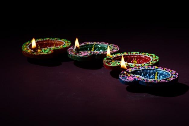 Kolorowe gliniane diya lampy (lampion) zaświecali podczas świętowania diwali. projekt karty z pozdrowieniami indian hindu light festival o nazwie diwali.