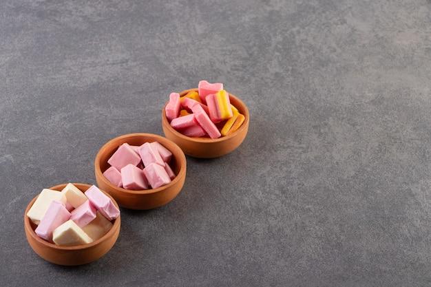Kolorowe gumy do żucia umieszczone na kamiennym stole.
