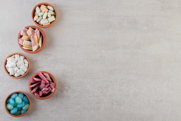 Kolorowe gumy do żucia w glinianych miseczkach ustawionych na kamiennym stole.