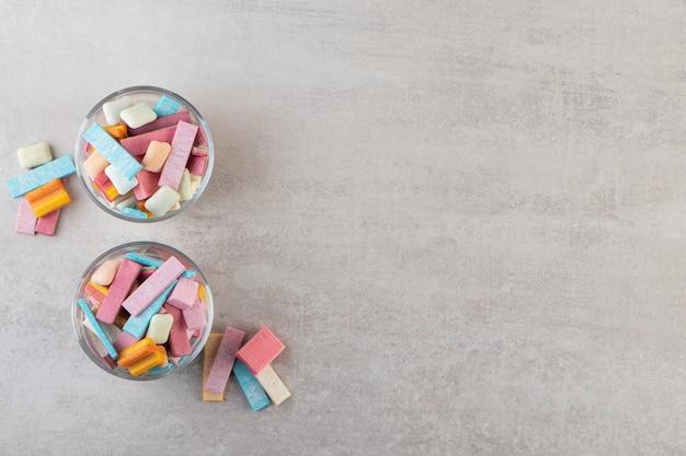 Kolorowe gumy do żucia w miseczkach postawionych na kamiennym stole.
