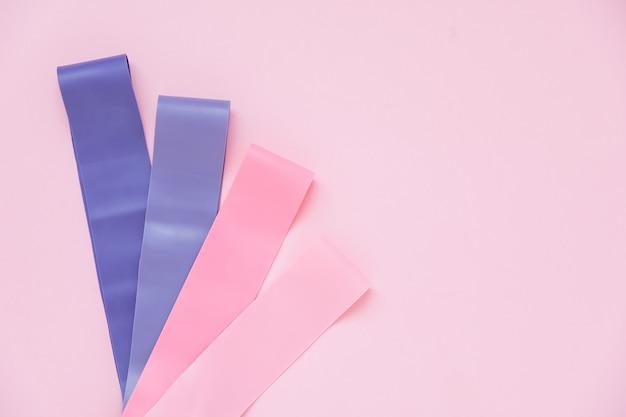 Kolorowe gumy ekspandujące fitness dla kobiet trenujących na różowym tle. proces odchudzania z treningiem cardio. sprzęt do ćwiczeń domowych. utrata masy ciała
