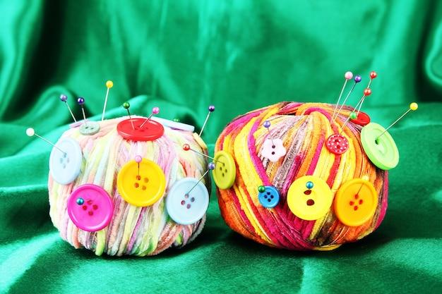 Kolorowe guziki i wielokolorowe wełniane kulki na kolorowej powierzchni tkaniny