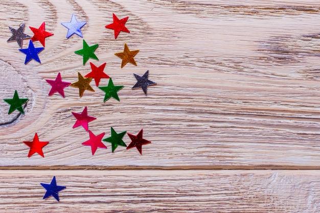 Kolorowe gwiazdki konfetti na drewniane tła.