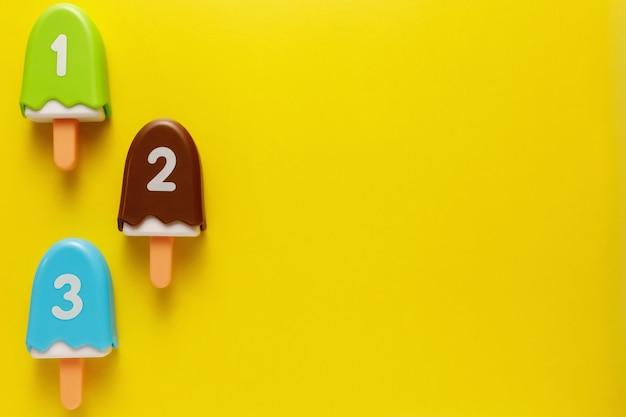 Kolorowe i różne plastikowe zabawki lody z numerami dla niemowląt na żółtym tle.