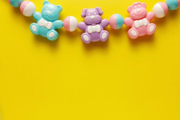 Kolorowe i różnorodne plastikowe zabawki dla dzieci na żółtym tle.