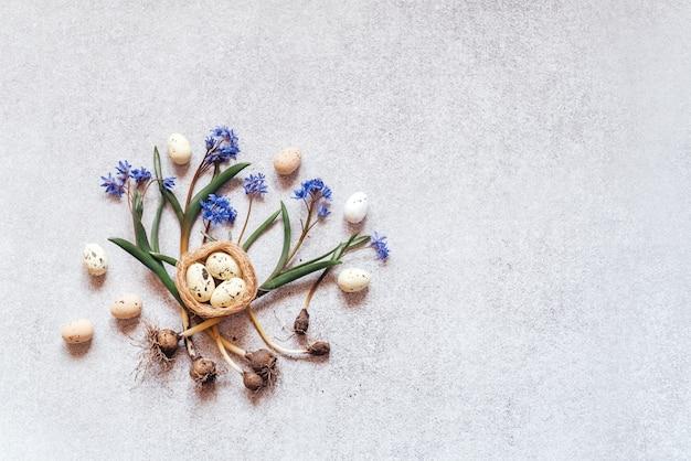 Kolorowe jaja wielkanocne gniazda ptaków i wiosenne kwiaty cebulicy niebieskiej