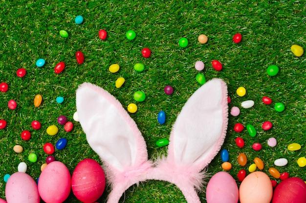 Kolorowe jajka i żywe cukierki na trawie. skład wielkanocny