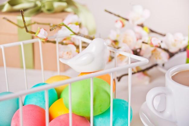 Kolorowe jajka na dzień wielkanocy w koszu. gałąź kwiat wiśni, filiżanka herbaty i pudełko