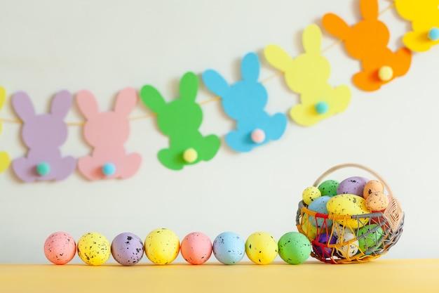 Kolorowe jajka w koszyku z ręcznie robioną girlandą wielkanocną bunny na tle netural. koncepcja wielkanocna.