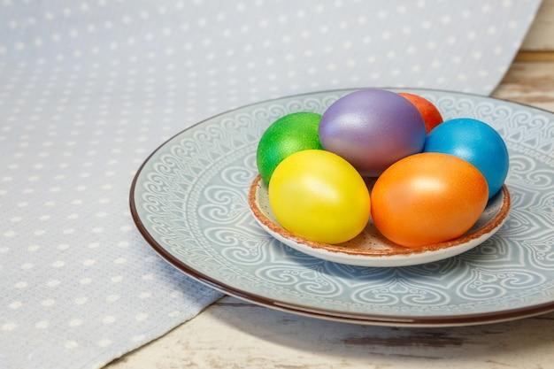 Kolorowe jasne pisanki na talerzu z ornamentem