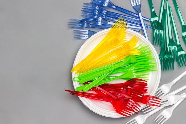 Kolorowe jednorazowe widelce plastikowe na białym talerzu