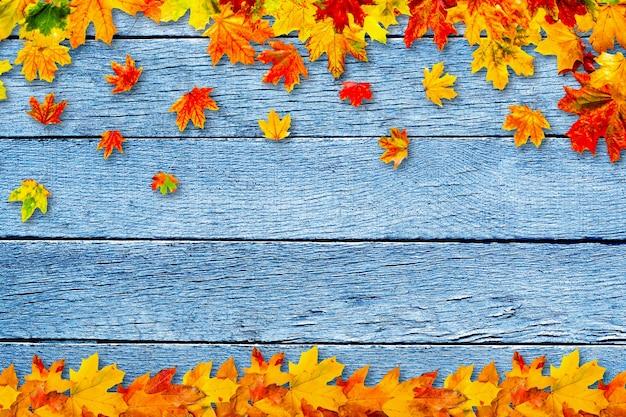 Kolorowe jesienne liście na drewnianym tle