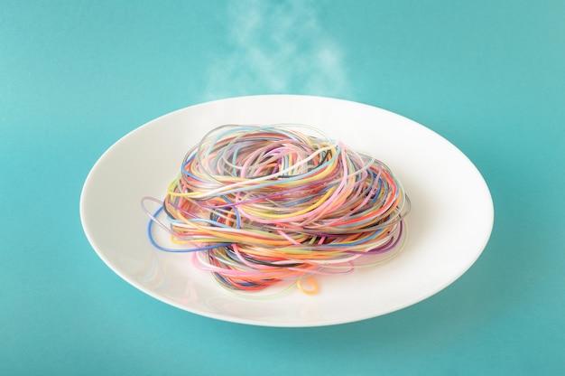 Kolorowe kable na talerzu, z którego na niebieskim tle wydobywa się para. koncept inspirowany spaghetti i jedzeniem. minimalistyczny styl fotografii.