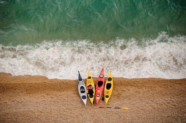 Kolorowe kajaki na piaszczystej plaży.