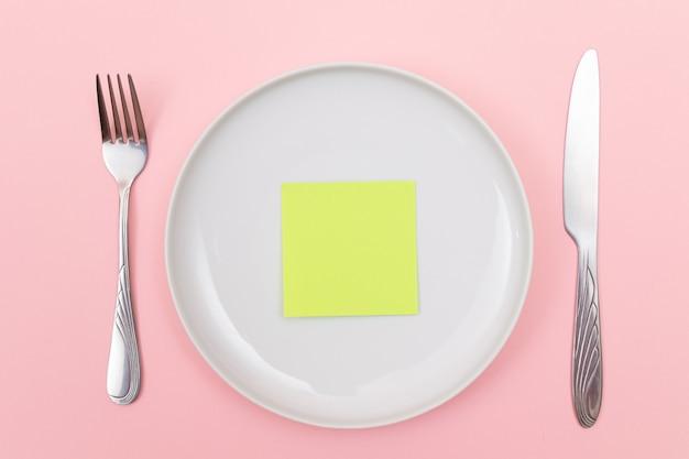 Kolorowe karteczki samoprzylepne lub papier do notatek na białym talerzu ceramicznym