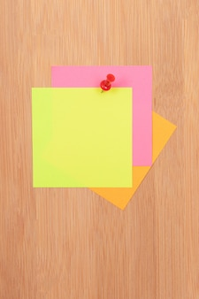 Kolorowe karteczki samoprzylepne przypięte do drewnianej tablicy ogłoszeń
