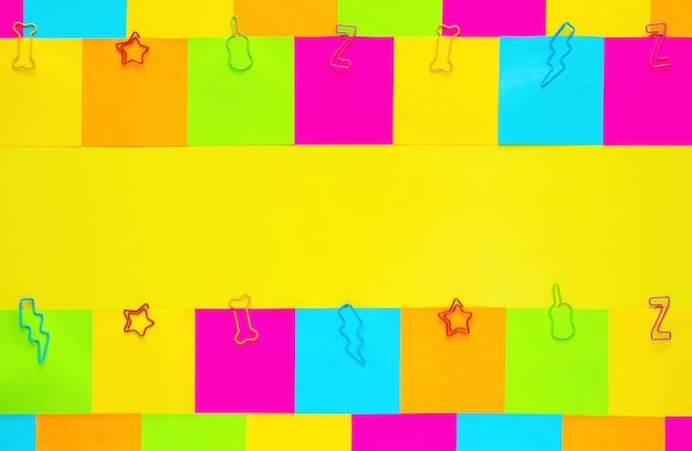 Kolorowe karteczki samoprzylepne z spinaczem do papieru na żółtym tle.