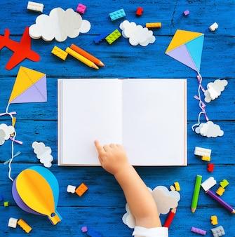 Kolorowe klocki zabawkowe, papierowe rękodzieła i pusta książka z rękami dziecka na niebieskim pokładzie drewna. kreatywne tło w szkole lub przedszkolu. koncepcja majsterkowania, budowy, zabawy edukacyjnej lub nauki języków