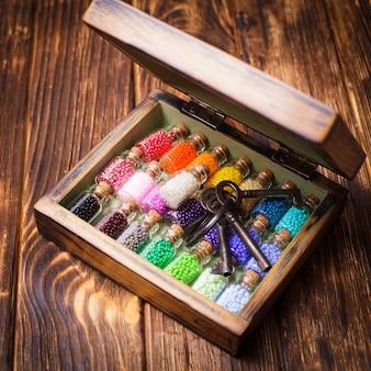 Kolorowe koraliki w mini szklanych butelkach w stylu retro. ręcznie robiony zestaw w pudełku