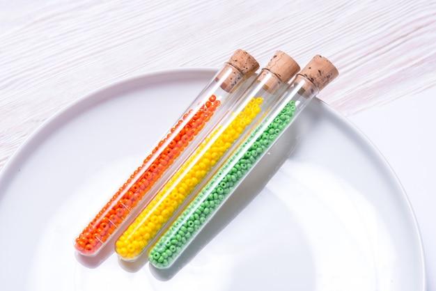 Kolorowe koraliki w szklanych butelkach