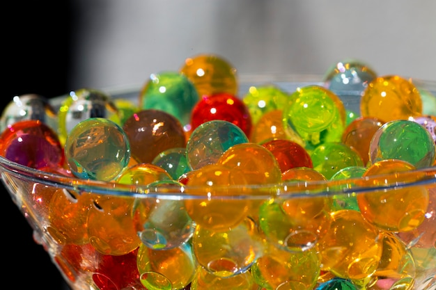 Kolorowe koraliki żelowe w zbliżeniu z selektywnym skupieniem, umieszczone w szklanym pojemniku, koncepcji tła lub tekstury