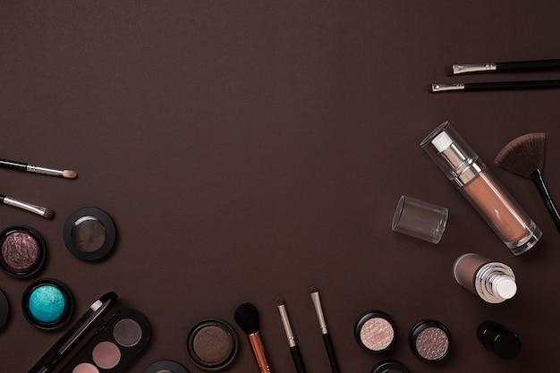 Kolorowe kosmetyki na brązowym miejscu pracy z kosmetykami do kopiowania tworzą obiekty artysty szminka do oczu ...