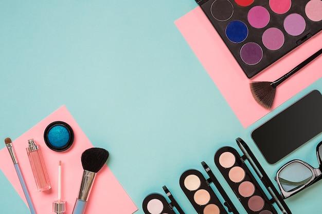 Kolorowe kosmetyki na niebieskim miejscu pracy z kopią kosmetyczną kosmetyki tworzą obiekty artysty szminka o...
