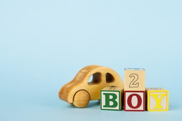 Kolorowe kostki z literami i cyframi oraz drewniany samochodzik