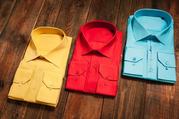 Kolorowe koszule męskie na drewnianym stole. trend w stylu casual.