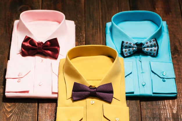 Kolorowe koszule męskie z muszką na drewnianym biurku