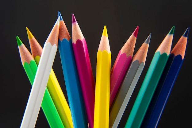 Kolorowe kredki do rysowania na ciemnym tle. edukacja i kreatywność. wypoczynek i sztuka