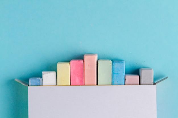Kolorowe kredki do rysowania na niebieskim tle. widok z góry. skopiuj miejsce kolor kreda