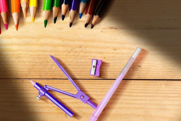 Kolorowe kredki i artykuły papiernicze z drewnianym stole tłem. powrót do koncepcji szkoły