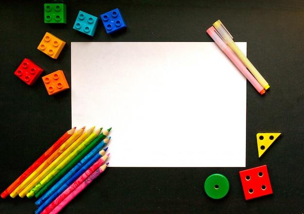 Kolorowe kredki i detale projektanta na tablicy szkolnej