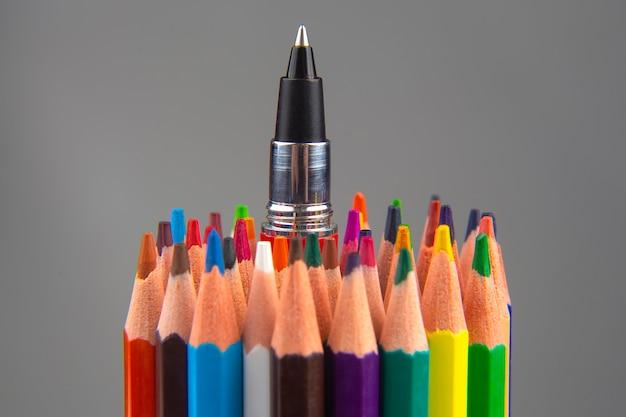 Kolorowe kredki i długopis do rysowania na szarym tle. edukacja i kreatywność. wypoczynek i sztuka