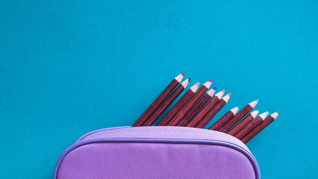 Kolorowe kredki i fioletowy woreczek