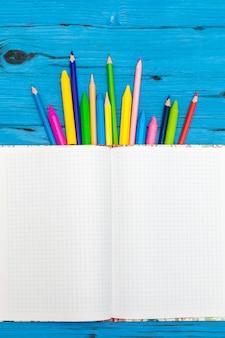 Kolorowe kredki i notatnik. koncepcja szkoły