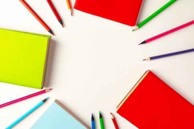 Kolorowe kredki i notesy na papierze