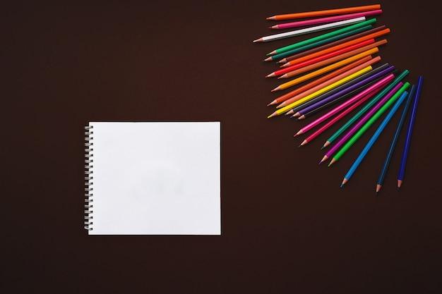 Kolorowe kredki i zeszyt szkolny na brązowym tle, powrót do koncepcji szkoły.