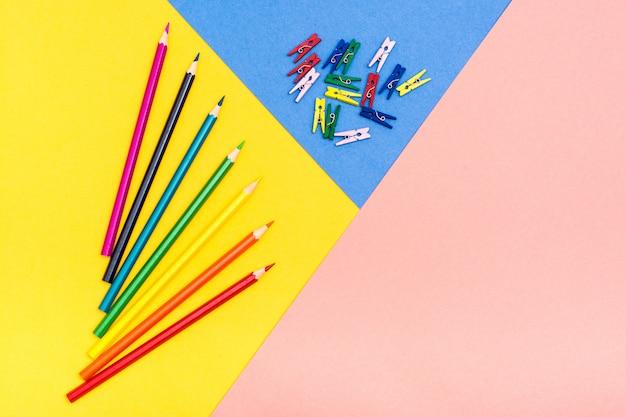 Kolorowe kredki leżą jak wachlarz na trójkolorowym tle