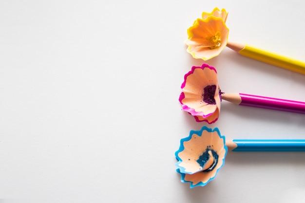 Kolorowe kredki na białym tle. wióry drzewne z ołówków.
