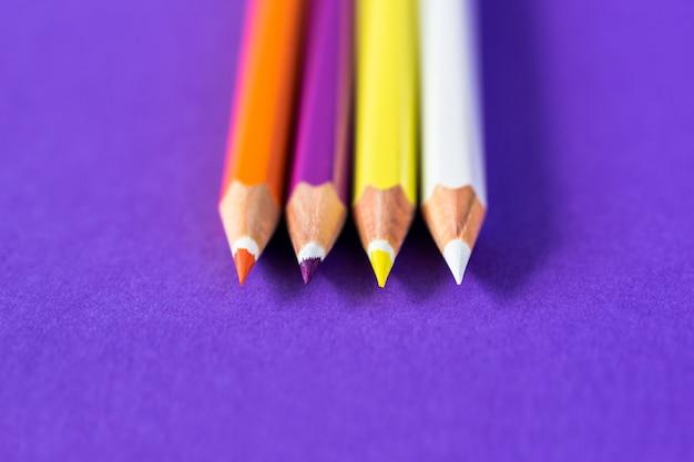 Kolorowe kredki na fioletowym tle z miejsca na tekst.